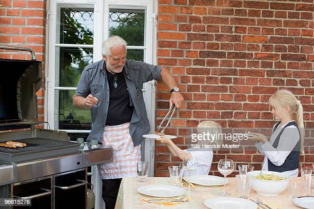 grandfather barbecuing for children
