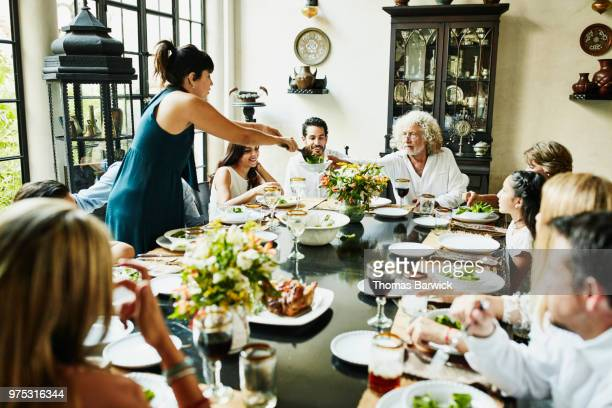 Grandfather being served food at dining room table during multigenerational family dinner