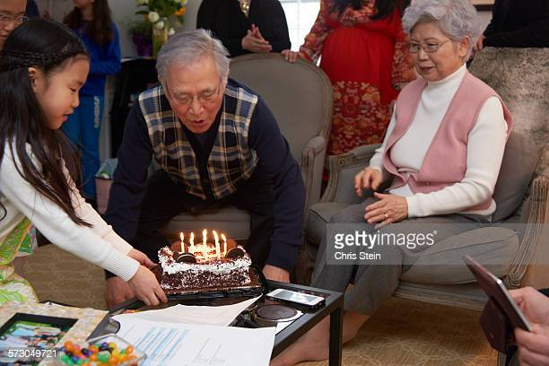 grandfather blowing out his birthday candles - scarsdale stock photos and pictures
