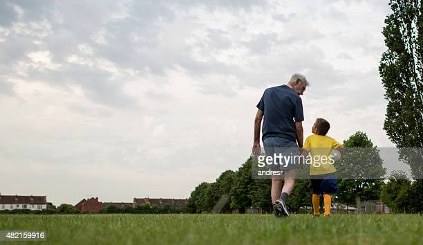 Grandfather bonding with his grandson playing football
