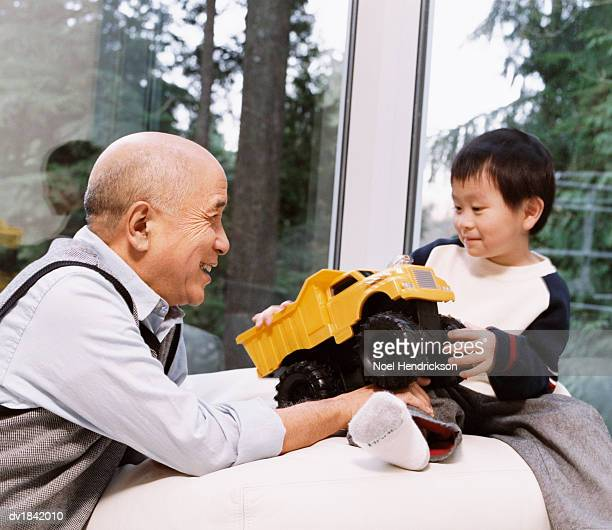 Grandfather Bonding with His Grandson who is Playing with a Toy Truck