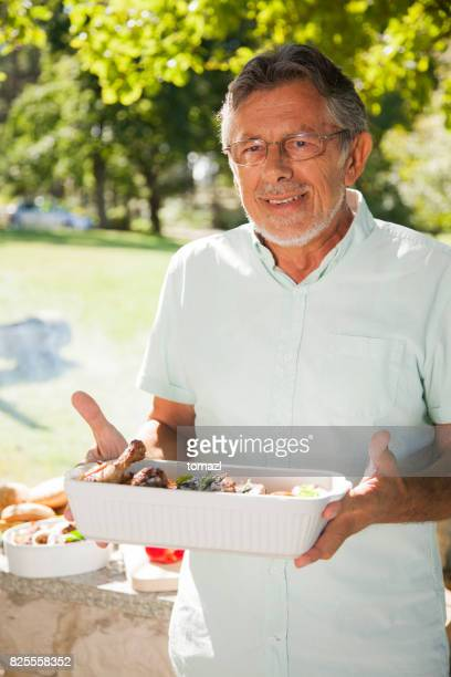 Grandfather bringing barbecue food