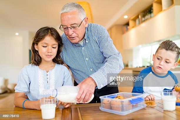 Abuelo presentado los nietos casero fresco galletas y leche