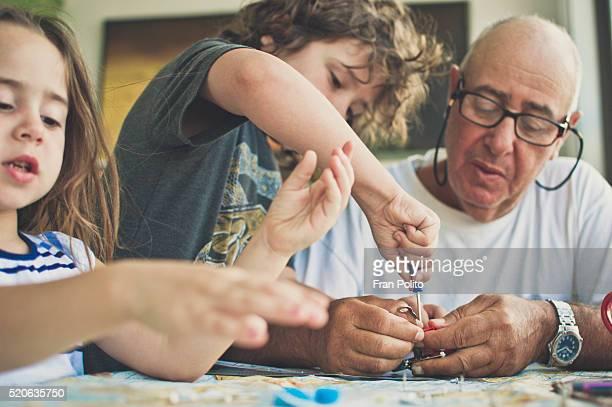 grandfather building a robot with his grandchildren. - ciencia y tecnología fotografías e imágenes de stock
