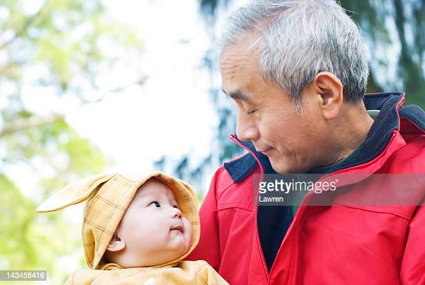 Grandfather carries baby in his arms in park