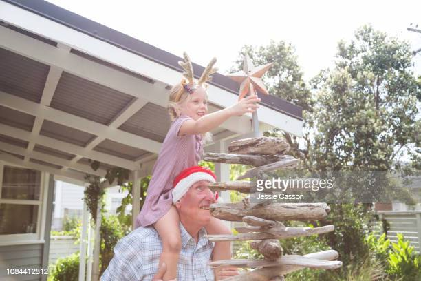 Grandfather carries granddaughter on shoulders to put the star on Christmas tree