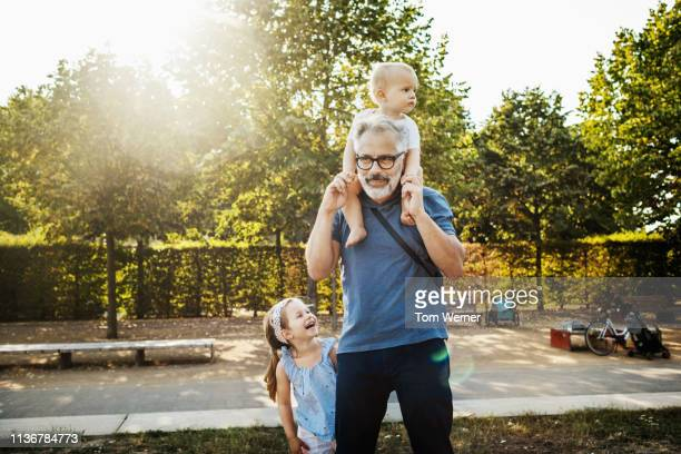 grandfather carrying grandson on his shoulders - carrying on shoulders stock pictures, royalty-free photos & images