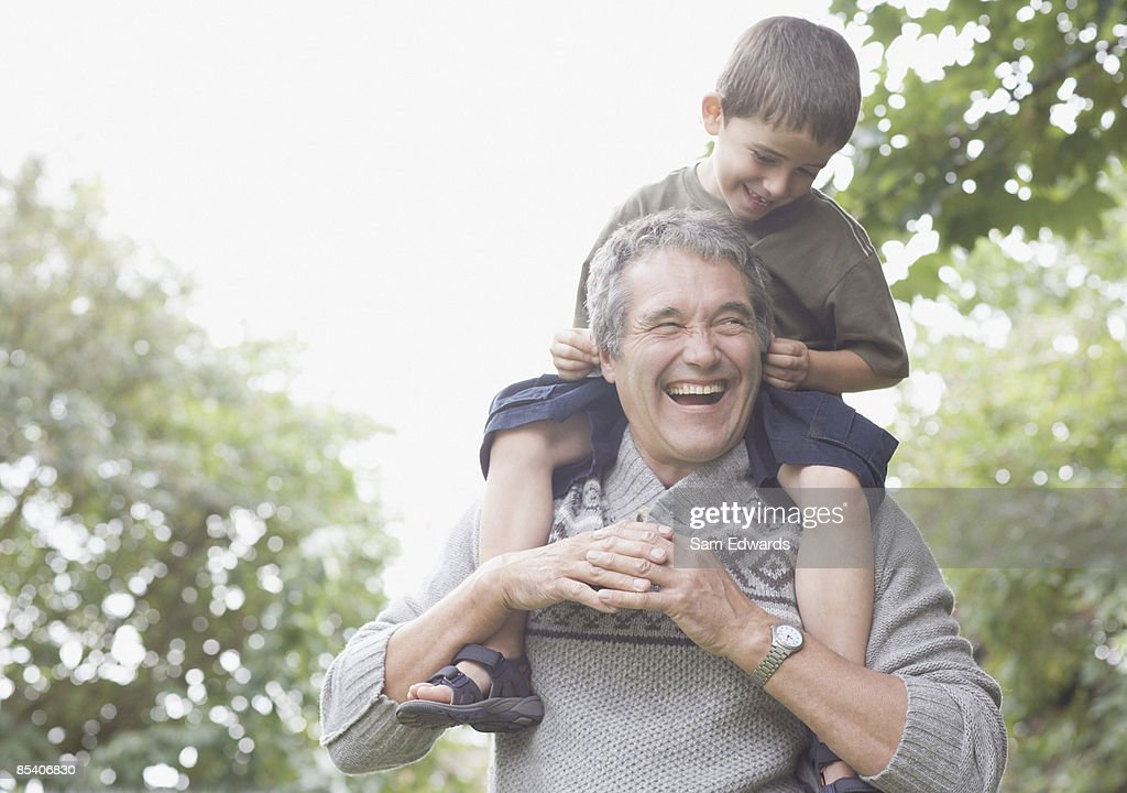 Grandfather carrying grandson on shoulders : Stock Photo