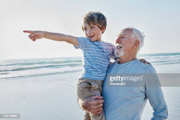 grandfather carrying grandson on the beach - grandfather stock pictures, royalty-free photos & images