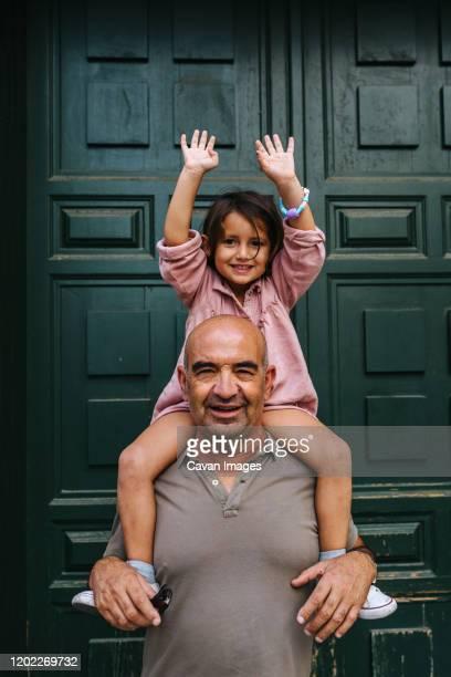 grandfather carrying his granddaughter on his shoulders, very happy a - portare a cavalluccio foto e immagini stock