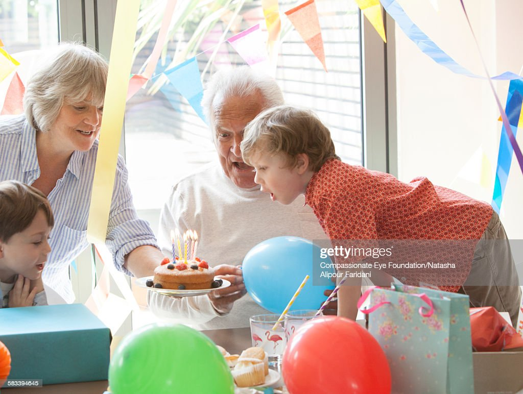 Grandfather celebrating birthday with family : Stock Photo