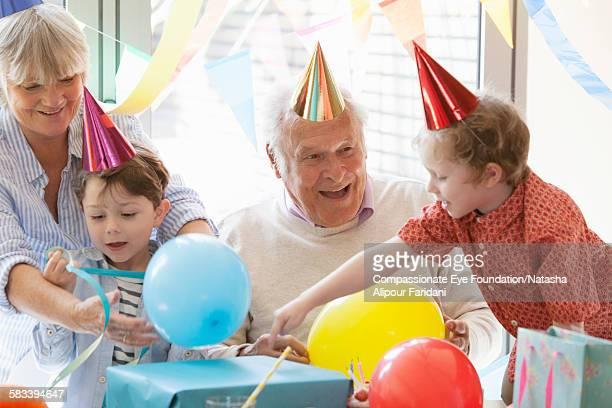 grandfather celebrating birthday with family - 80代 ストックフォトと画像