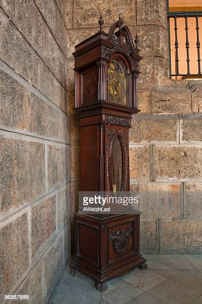 Grandfather clock along a stone wall in the corner