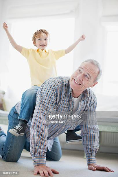 Grandfather crawling with grandson on back
