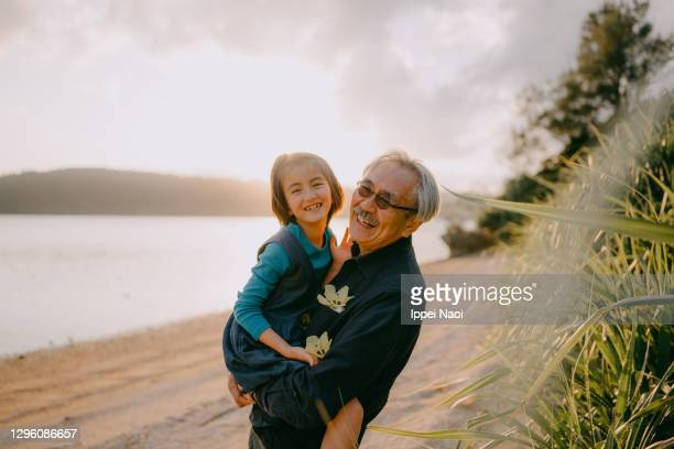 grandfather cuddling granddaughter on beach at sunset, japan - grandfather stock pictures, royalty-free photos & images