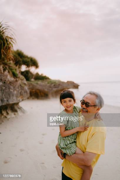 grandfather cuddling granddaughter on beach at sunset - ippei naoi stock pictures, royalty-free photos & images