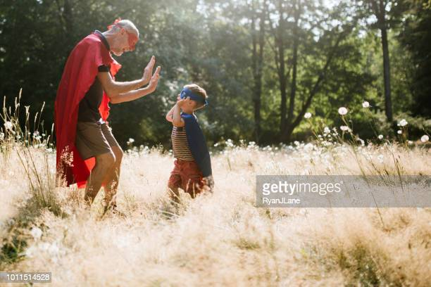 grandfather dressed as superhero plays outside with grandson - hero stock photos and pictures