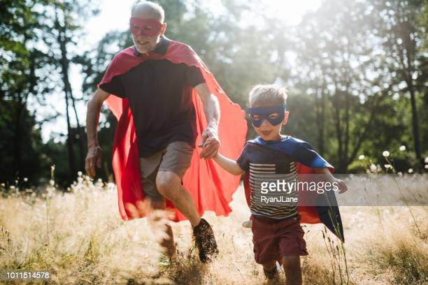 grandfather dressed as superhero plays outside with grandson - superhero stock pictures, royalty-free photos & images