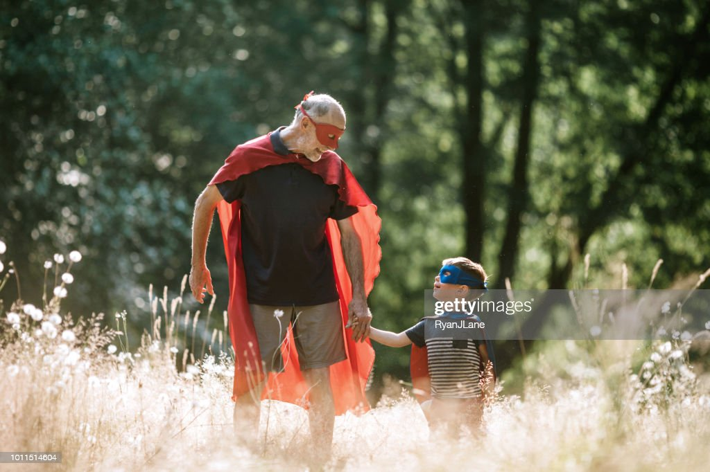Grootvader verkleed als superheld speelt buiten met kleinzoon : Stockfoto