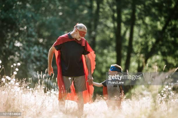 Grootvader verkleed als superheld speelt buiten met kleinzoon