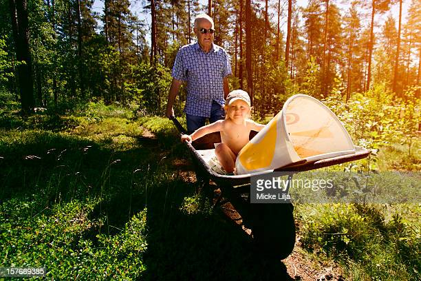 Grandfather drives grandson in a wheelbarrow
