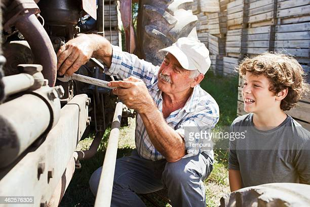 Grandfather eaching grand son how to fix tractor.