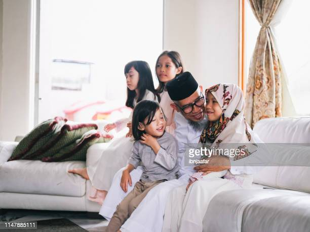 grandfather embrace grandchild - hari raya celebration stock pictures, royalty-free photos & images