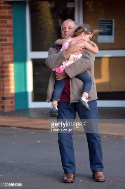 grandfather embracing his granddaughter - rafael ben ari stock-fotos und bilder