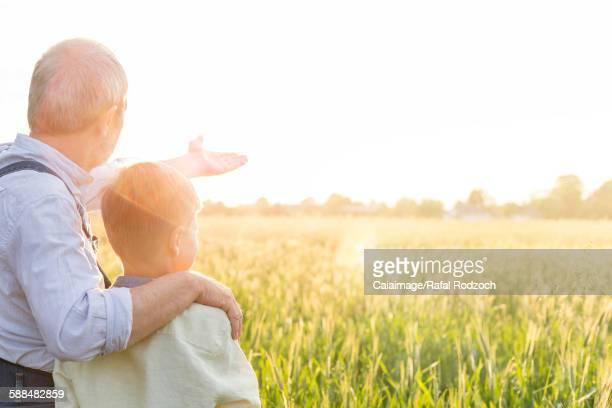 Grandfather farmer explaining rural wheat crop to grandson