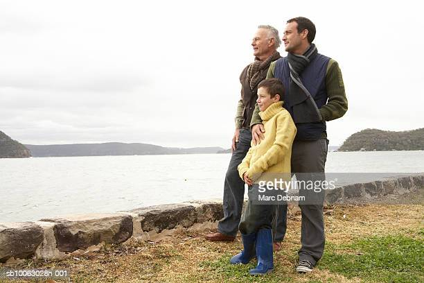 Grandfather, father and boy (10-11) standing at edge of lake looking at view, side view