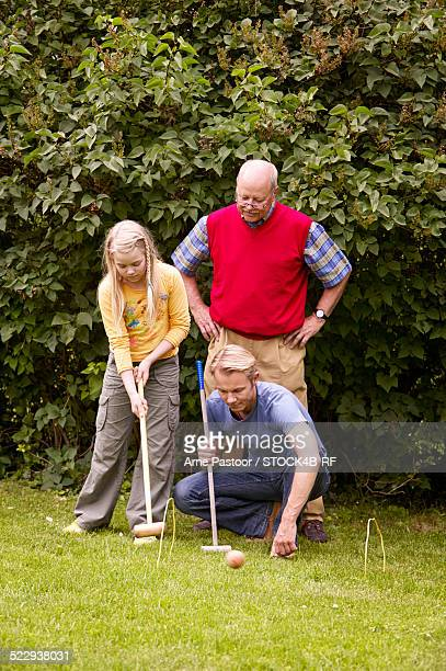 'Grandfather, father and daughter playing crocket in garden'