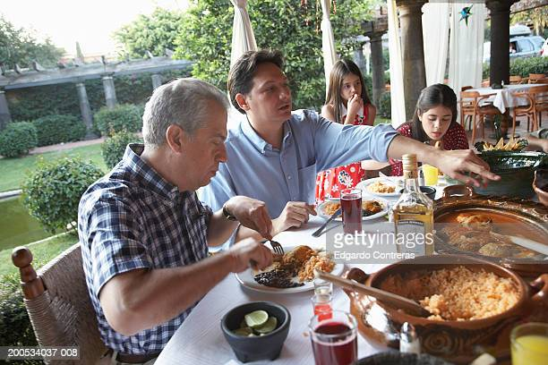 Grandfather, father and daughters (7-15) having dinner on patio
