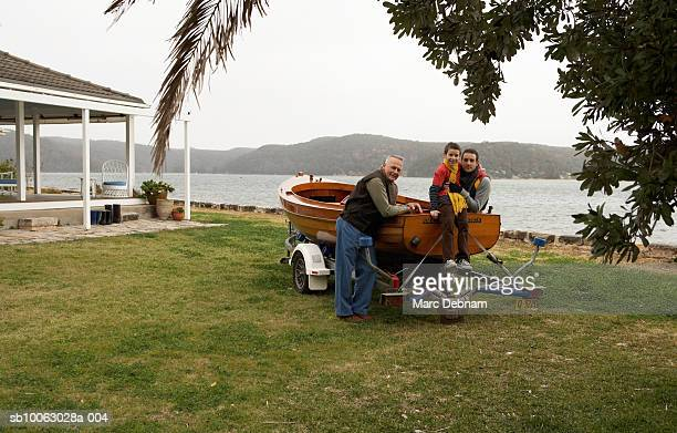 Grandfather, father and grandson (10-11) around boat on trailer near lake