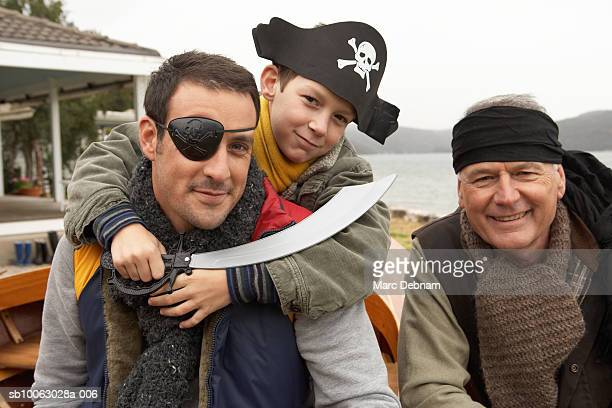 Grandfather, father and grandson (10-11) wearing pirate costumes outdoors, portrait