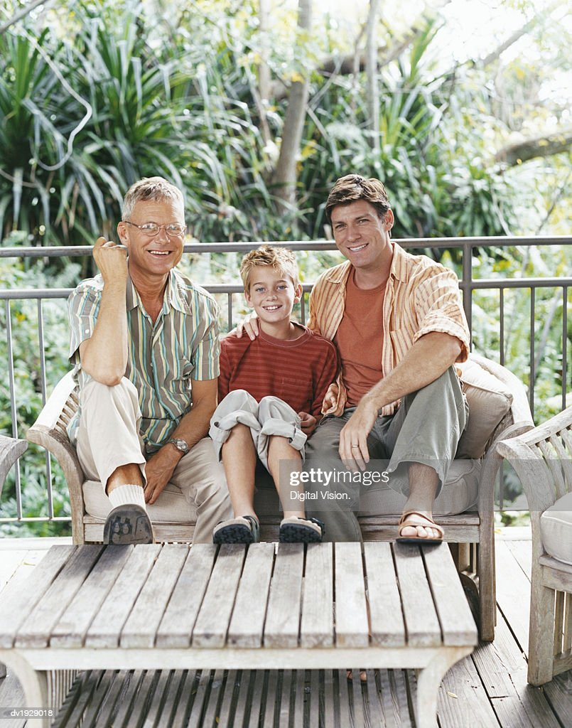 Grandfather, Father and Son Sitting on a Bench on Their Porch : Stock Photo