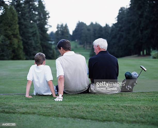 Grandfather, father and son (8-10) sitting on golf course, rear view