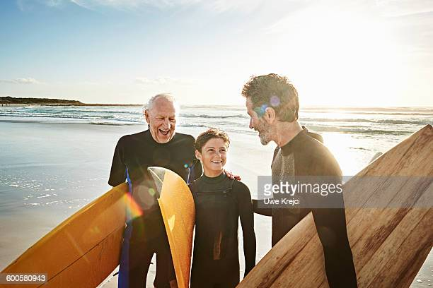 Grandfather, father and son surfing