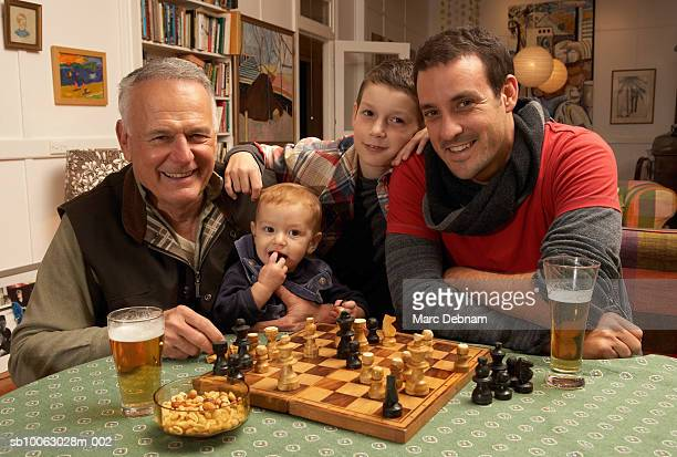 Grandfather, father, boy (10-11) and baby girl (12-15 months) sitting at table with chessboard at home, portrait