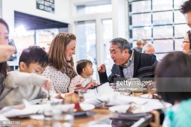 Grandfather feeding cake to baby girl while sitting with family in restaurant