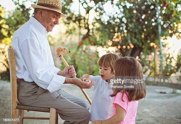 Grandfather gives candy to his grand children