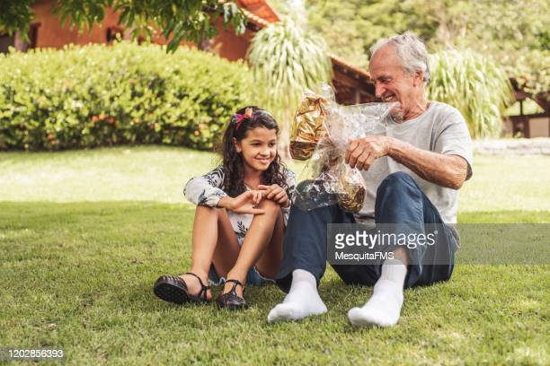 grandfather giving easter egg to his granddaughter - easter sunday stock pictures, royalty-free photos & images