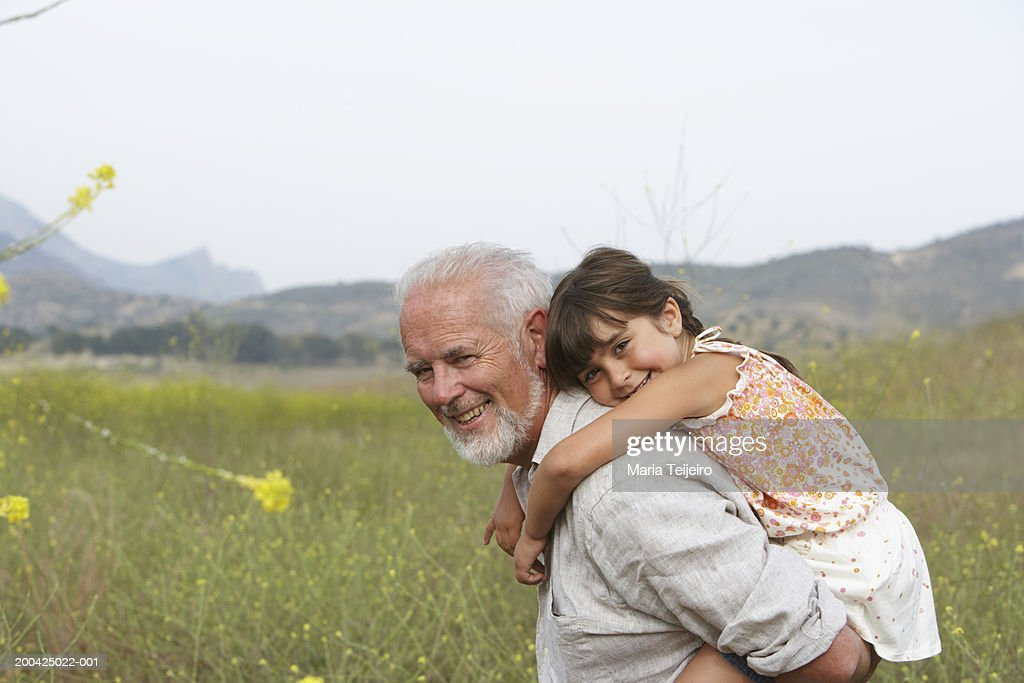 Grandfather giving girl (4-6) piggyback, smiling, portrait, side view : Bildbanksbilder