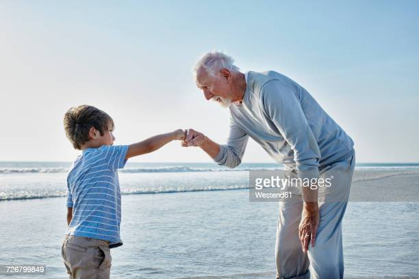 grandfather giving grandson a fist bump on the beach - fist bump stock pictures, royalty-free photos & images