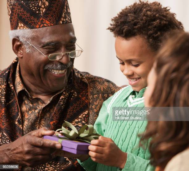 grandfather giving grandson kwanzaa gift - kwanzaa stock pictures, royalty-free photos & images