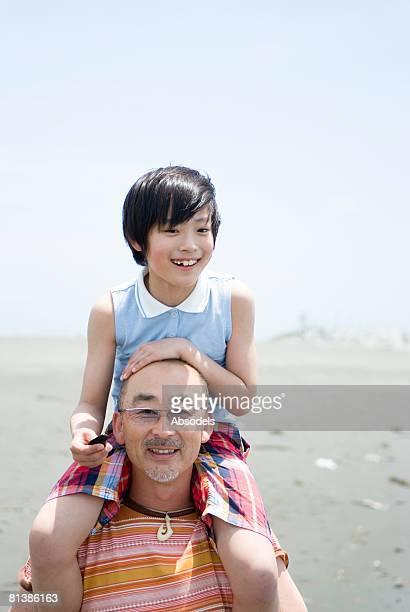 Grandfather giving his grandson (8-9) a piggyback on beach
