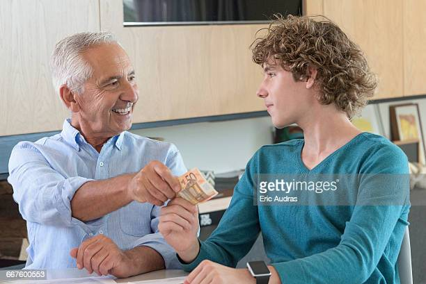 Grandfather giving teenage grandson pocket money
