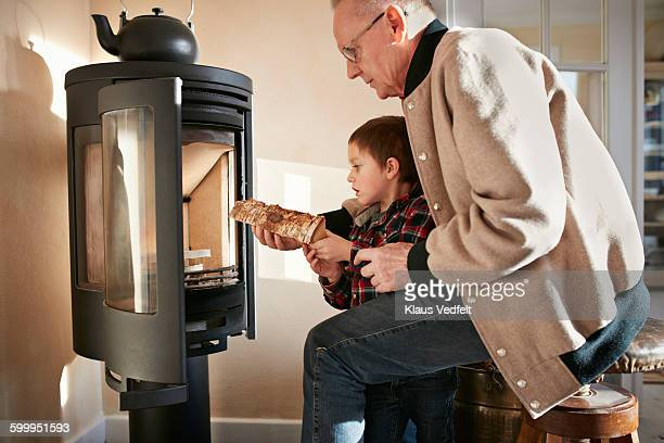 grandfather & grandson building a fire - wood burning stove stock photos and pictures
