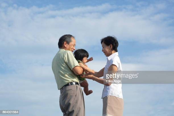 Grandfather handing granddaughter to grandmother in the open air