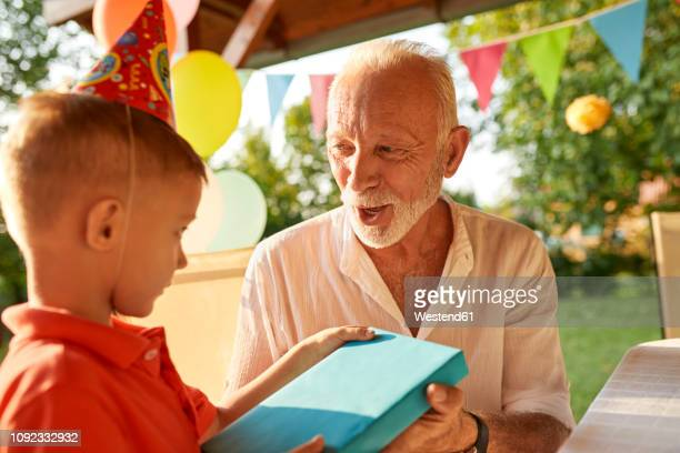 grandfather handing over present to grandson on a garden birthday party - birthday present stock pictures, royalty-free photos & images