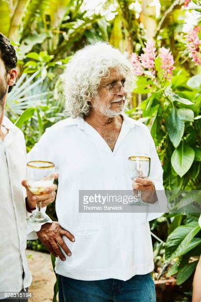 Grandfather hanging out with family during backyard dinner party